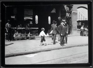 Lewis Hine, Candid shot of Newsie selling papers on street, 1912.jpg